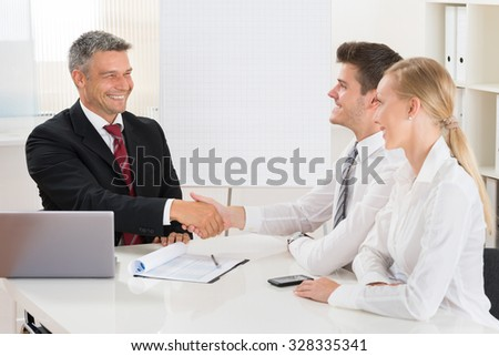 Estate Agent Shaking Hands With Young Happy Couple At Desk - stock photo
