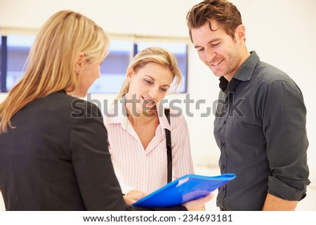 Estate Agent Showing Empty Office Space To Clients - stock photo