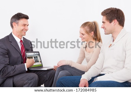 Estate Agent Showing House On Laptop To Young Couple Sitting At Home - stock photo