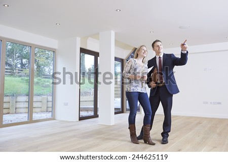 Estate Agent Showing Prospective Female Buyer Around Property - stock photo