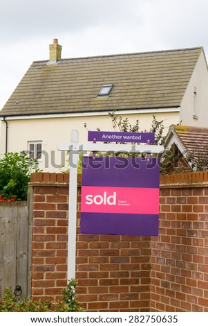 Estate agent 'Sold' sign outside an English house vertical image - stock photo