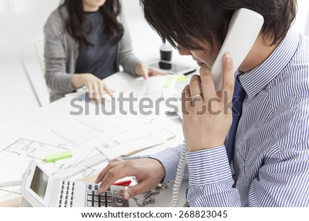 Estate agent talking on phone with buyer in background in the office