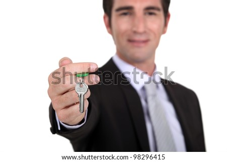 Estate agent with a house key - stock photo