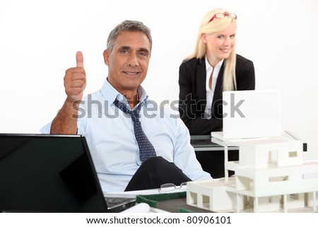 Estate agent with thumbs up - stock photo