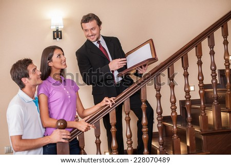 Estate agent with young couple on ladder. three going up to second floor on wooden ladder to see house - stock photo