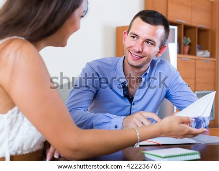 Estate american agent explaining offer to client and smiling in office