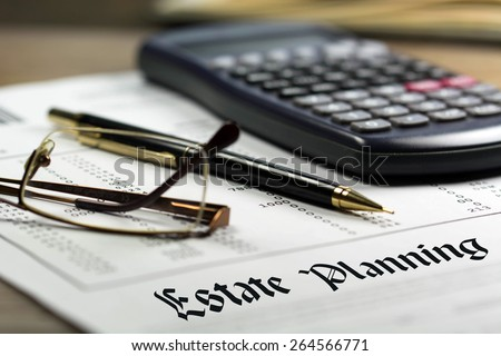Estate planning. Calculator, glasses and black pen on financial documents in the background.  - stock photo