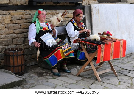 ETAR, BULGARIA - JUNE 19, 2016: Two aged Bulgarian women spin and knit outside the house