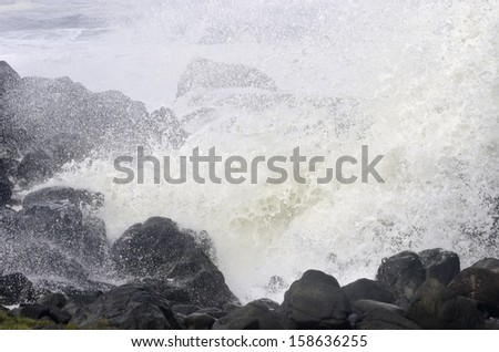 Eternal conflict: Ocean wave exploding against volcanic rocks along Pacific coast of Oregon - stock photo