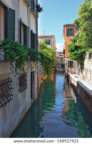 Eternal fantastic Venice. Narrow street - the channel. In water the dark blue sky is reflected. Windows of ground floors are closed by figured lattices.