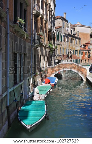 Eternal fantastic Venice. The narrow street - channel is brightly shined by the midday sun. At a wall gondolas are moored