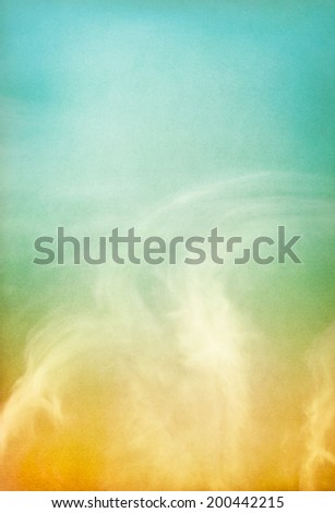 Ethereal and wispy clouds on a paper background with a color gradient.  Image has a pleasing paper grain and texture visible at 100 percent.
