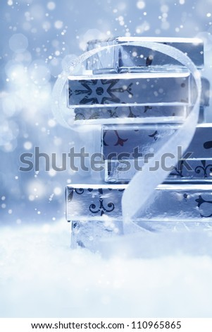 Ethereal festive background with a stack of silver Christmas gift boxes with a decorative ribbon in falling snow - stock photo
