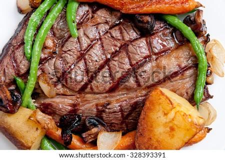 ethically raised, fresh cut organic rib eye steak grilled rare with fresh roasted vegetables