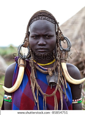 ETHIOPIA - AUG 11: Unidentified Mursi woman posing in the village, the ethnic groups in the The Omo valley Could disappear Because of Gibe III hydroelectric dam on Aug 11, 2011 in Omo Valley, Ethiopia. - stock photo