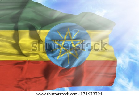 Ethiopia waving flag against blue sky with sunrays - stock photo