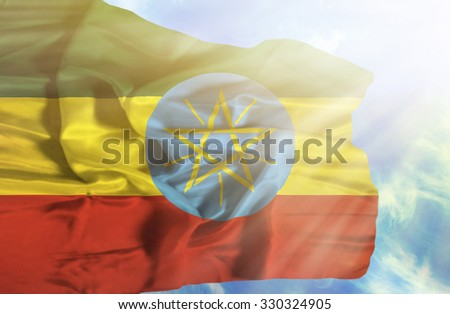 Ethiopia waving flag against blue sky with sunrays - stock photo
