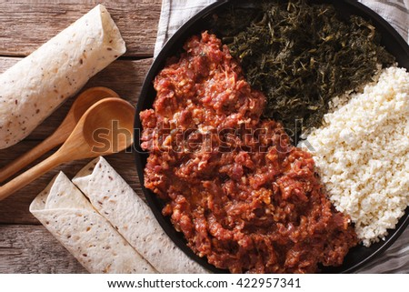 Ethiopian cuisine: kitfo with herbs and cheese on a plate and injera. Horizontal view from above