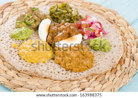 Ethiopian Feast - Injera (sourdough flatbread) with doro wat (red chicken stew), yebeg alicha (mild lamb stew), misir wat (red lentils puree), kik alicha (yellow split peas) and gomen (collard greens) - stock photo
