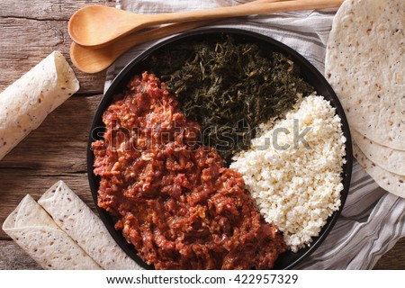Ethiopian kitfo: marinated beef with herbs and cheese close-up on a plate and injera. horizontal view from above