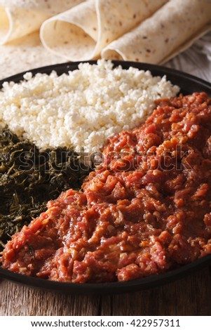 Ethiopian kitfo with herbs and cheese ayibe on a plate and injera close-up. Vertical