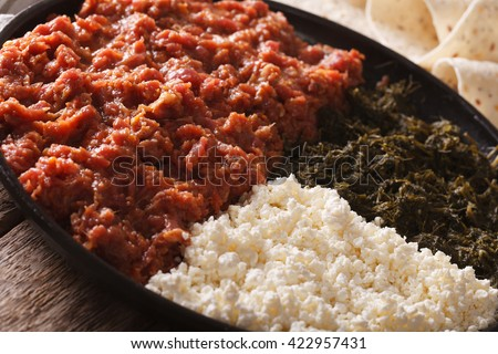 Ethiopian kitfo with herbs and cheese ayibe on a plate close-up. horizontal