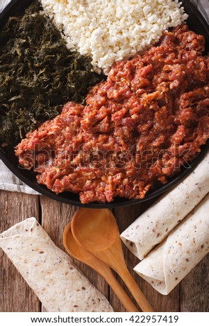 Ethiopian kitfo with herbs and cheese ayibe on a plate close-up. vertical view from above
