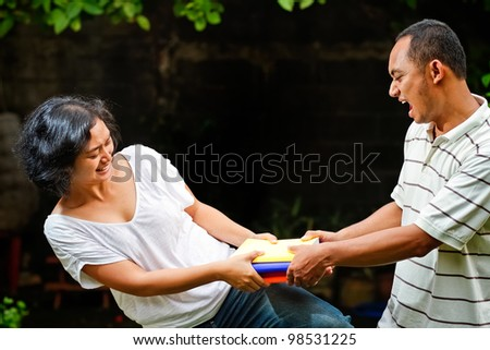 ethnic asian male and female students struggle for stack of books - stock photo