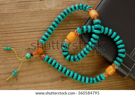 Ethnic beads of various colors on a wooden background