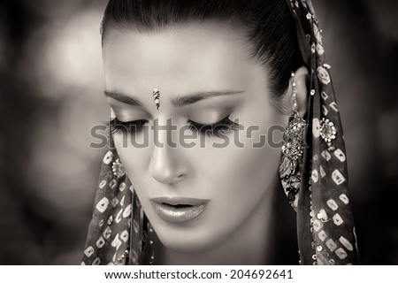 Ethnic beauty. Beautiful hindu woman with traditional clothes, jewelry and makeup. Closeup portrait in black and white - stock photo