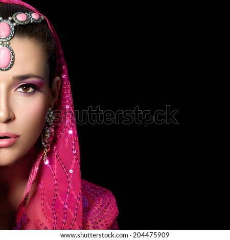 Ethnic beauty. Beautiful hindu woman with traditional clothes, jewelry and makeup covering half face with one hand. Portrait isolated on black - stock photo