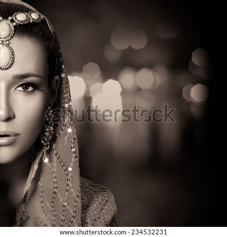 Ethnic Beauty Fashion. Beautiful hindu woman with traditional clothes, jewelry and makeup. Monochrome half face portrait with copy space for text - stock photo