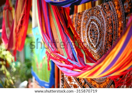 Ethnic blankets and hammocks with aztec various pattern hanging in street market - stock photo