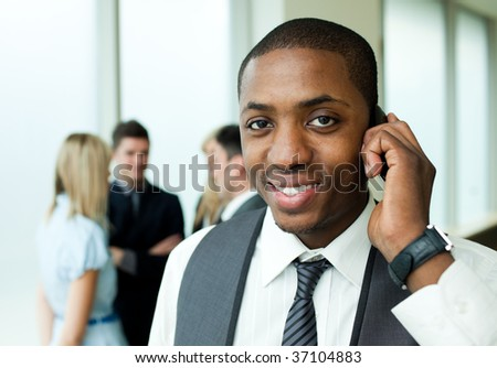 Ethnic businessman on phone in office with his team in the background