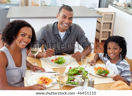 Ethnic couple dining with their son in the kitchen - stock photo