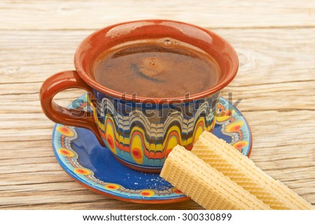 Ethnic cup of coffee and Wafer biscuit on the beautiful old wooden background