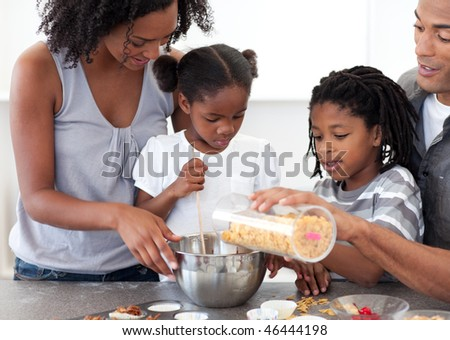 Ethnic family making biscuits together in the kitchen - stock photo