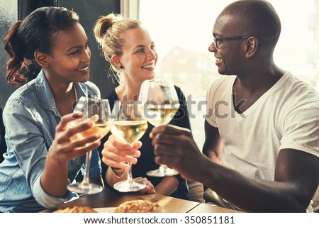 Ethnic friends at a bar drinking wine and eating tapas - stock photo