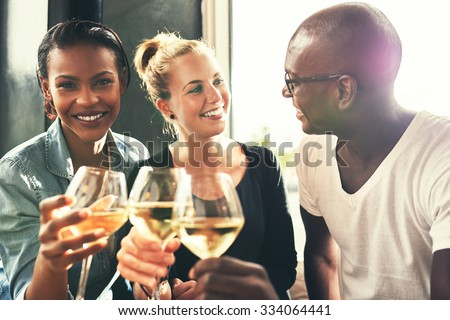 Ethnic friends drinking wine at a bar having a good time laughing - stock photo