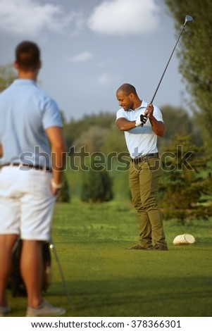 Ethnic male golfer teeing golf ball, swinging golf club. - stock photo