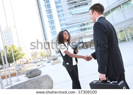 Ethnic Man and Woman Business Team shaking hands at office building - stock photo