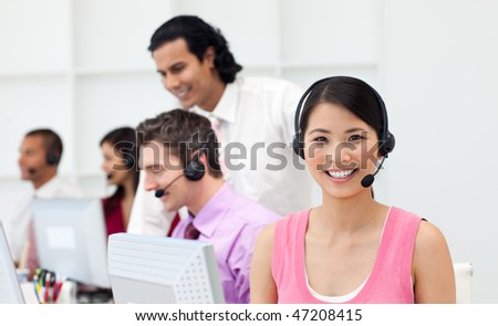 Ethnic manager checking his employee's work in a call center - stock photo