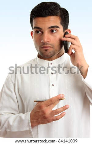 Ethnic mixed race businessman wearing traditional robe is using a mobile phone and looking sideways. - stock photo