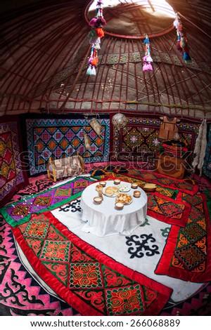 Ethnic nomadic house yurt interior with table of national food at Nauryz celebration - stock photo