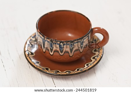 Ethnic plate and cup on wooden background close up