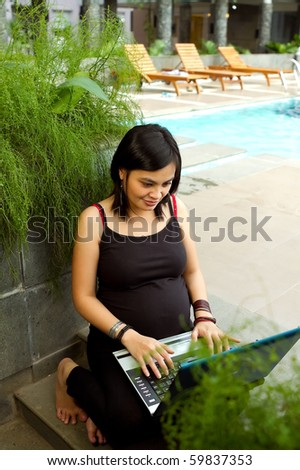 Ethnic pregnant business woman happy working with laptop - stock photo