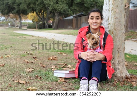 Ethnic teenage girl playing with a dog under a tree in the park with books and school backpack - stock photo