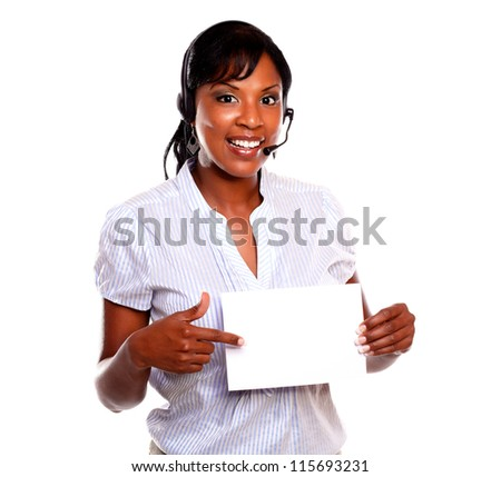 Ethnic woman wearing headphones pointing and holding white card while is looking at you on isolated background - copyspace - stock photo