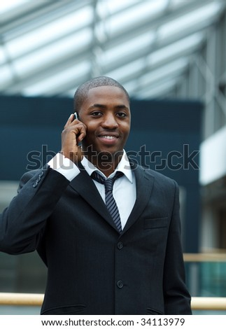 Ethnic young businessman speaking on phone and smiling at the camera - stock photo