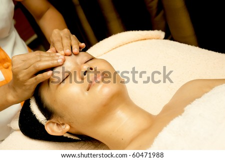 Ethnic young woman having face massage at beauty clinic - stock photo